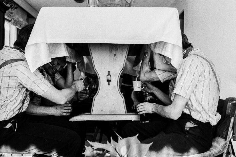 Silvesterchläuse heben einen Holztisch in die Höhne und prosten sich zu.