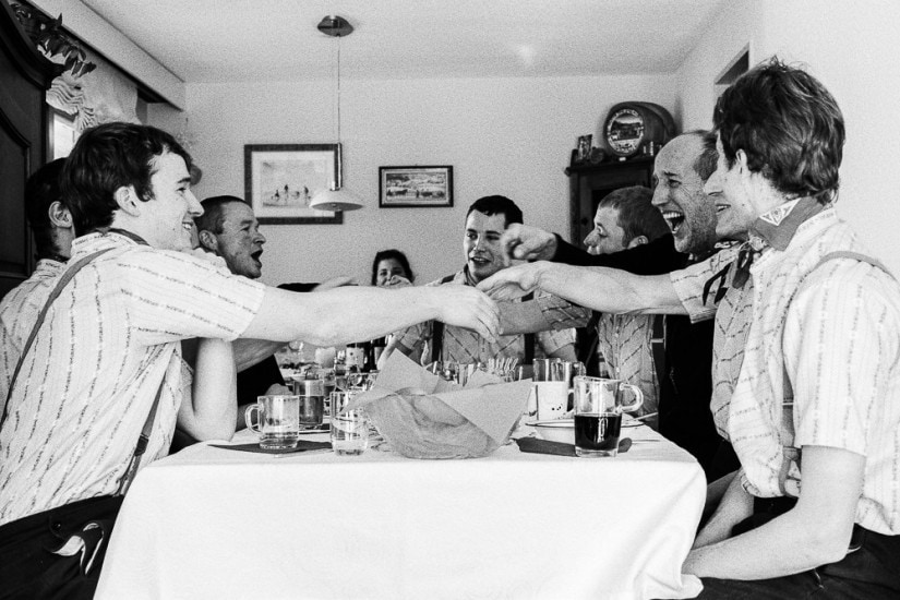 Silvesterchläuse sitzen an einem Tisch und singen beim Znüni.