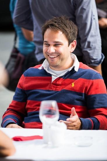 lachender Mann im rot blau gestreiften Pullover.