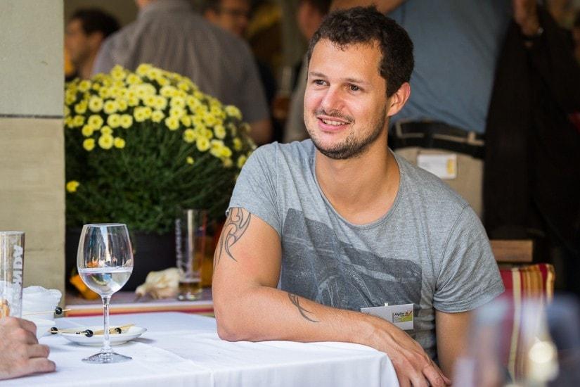Mann im grauen T-Shirt und Tatoos. sitzt beim Aperitif.