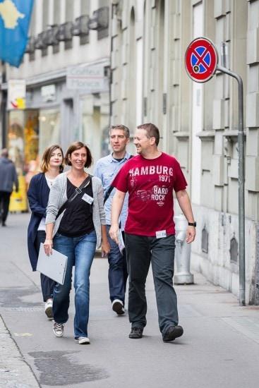 Eine Gruppe von vier Personen läuft durch Bern.