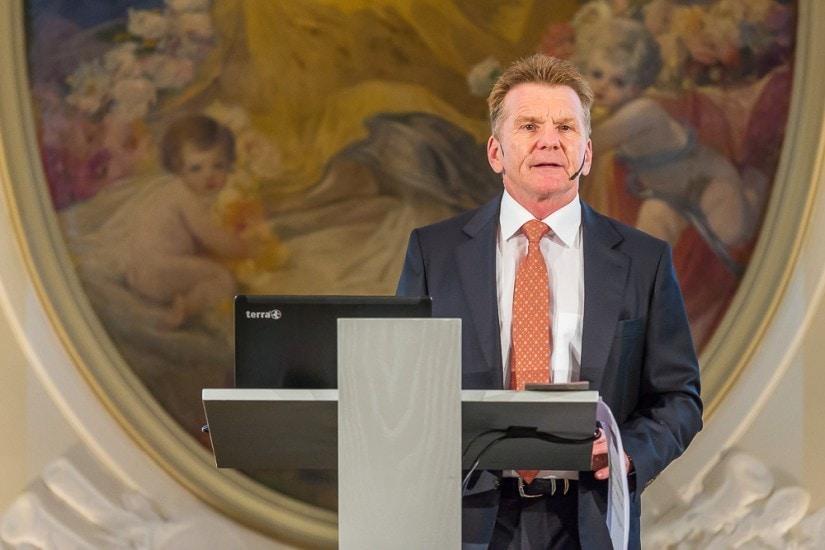 Mann am Rednerpult spricht zum Publikum.