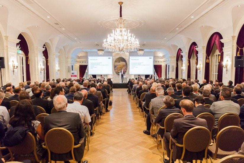 Grosser Saal mit vielen sitzenden Personen.