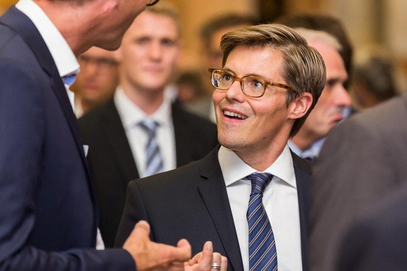junger Mann mit Brille in einer Diskussion.