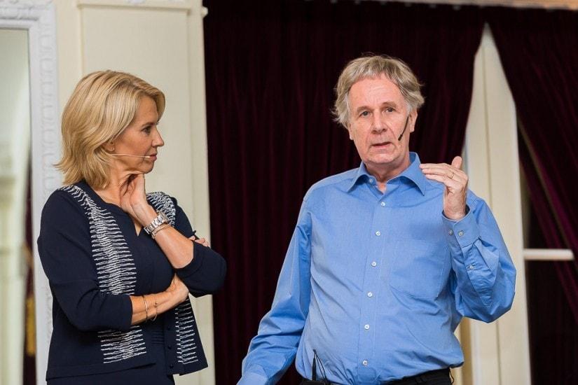 """Frau namens """"Christine Maier"""" hört einem Mann im blauen Hemd beim sprechen zu."""