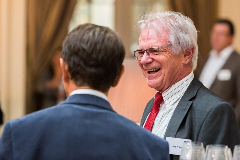 Lachender Mann mit roter Krawatte.