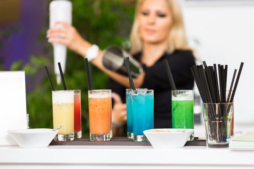 farbige Gläser auf einem Tisch, im Hintergrund steht die Barfrau.