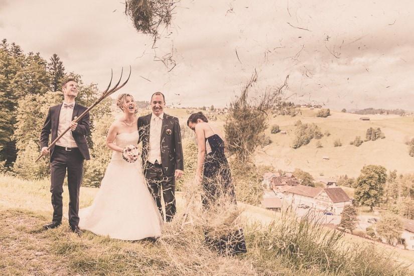 Trauzeugen werfen Heu in die Luft. Brautpaar muss lachen.