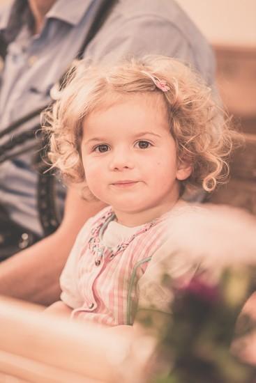 Fröhliches Mädchen sitzt auf der Kirchbank.