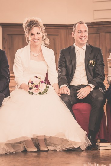 lachendes Brautpaar sitzt in der Kirche Hemberg.