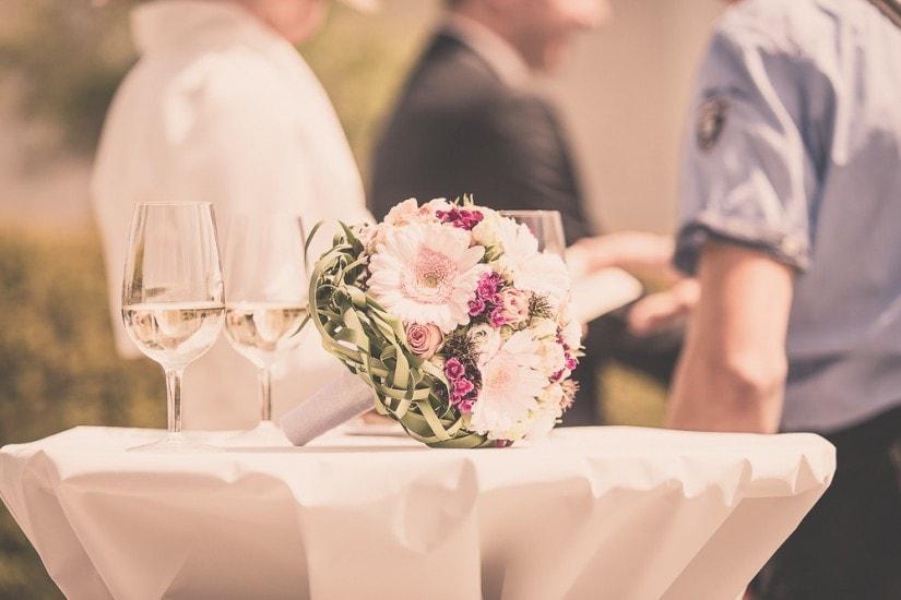 Brautstrauss und zwei Wassergläser stehen auf einem Bistrotisch.