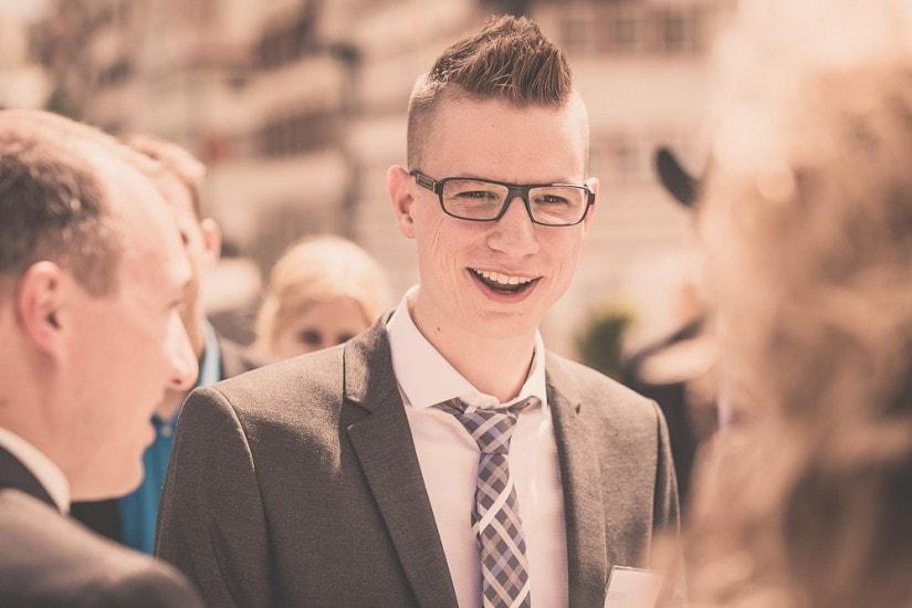 Mann mit Brille und Krawatte gratuliert dem Hochzeitspaar.