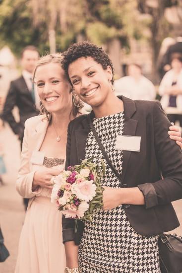 Zwei lachende Hochzeitsgäste (Frauen) beim Apéro. Die eine hält den Brautstrauss.