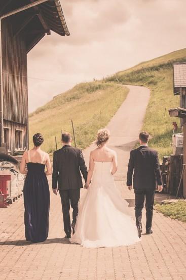Brautpaar flankiert von Trauzeugen laufen eine Strasse hoch.