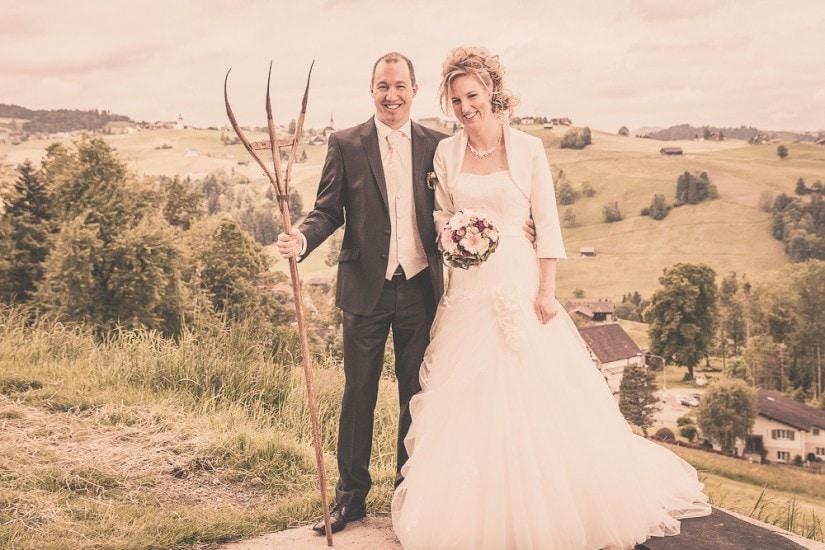 Lachendes Brautpaar mit alter Heugabel und Brautstrauss.