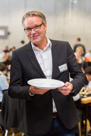lachender Mann mit leerem Teller in der Hand.