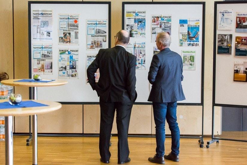 Zwei Männer stehen vor einer Pinnwand und begutachten alte Zeitschriften.