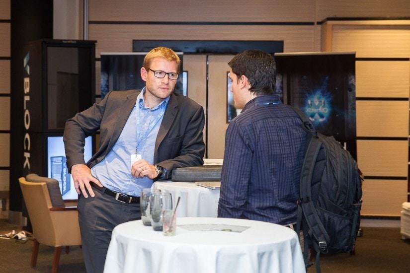 Zwei Männer stehen an einem Bistrotisch mit weissem Tischtuch.