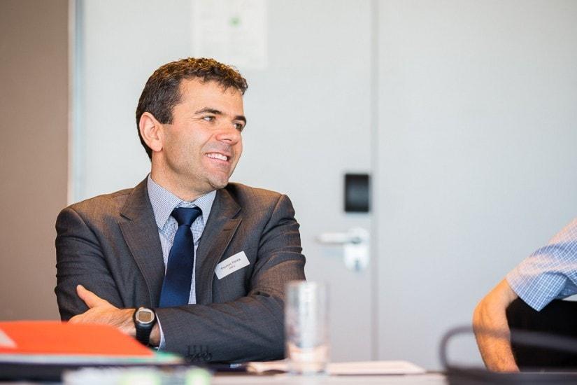 lachender Mann in einem Sitzungszimmer.