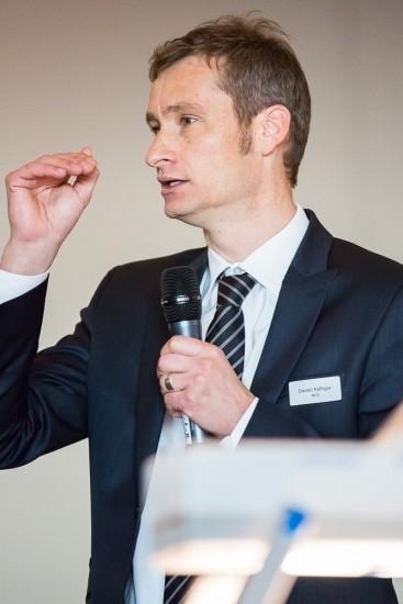 Mann im Anzug spricht in ein Mikrofon.