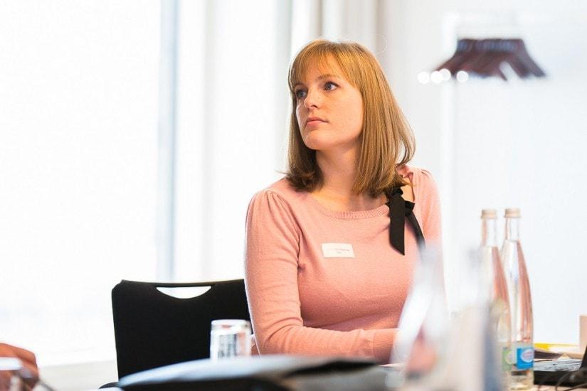 Frau mit rosa Pullover sitzt in einem Sitzungssaal.