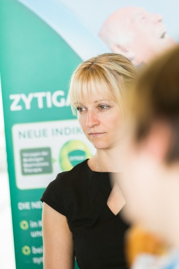 Blonde Frau vor grünem Werbebanner.