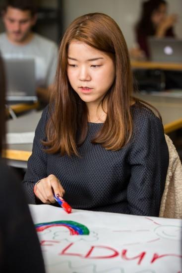 Studentin schreibt etwas auf ein Plakat.
