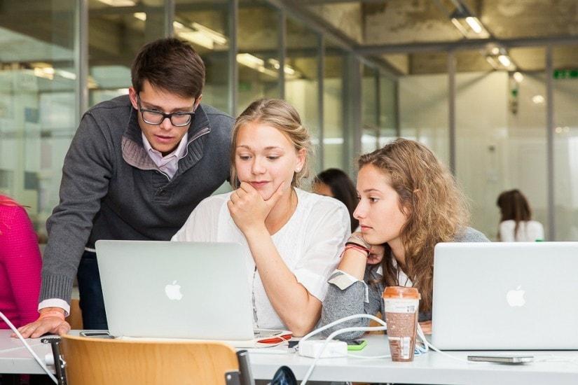 Drei Studenten sitzen um einen Computer.