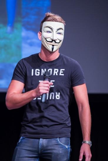 Mann mit Vendetta Maske und Mikrofon.