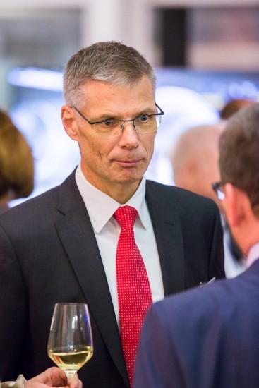 Mann mit Anzug, roter Krawatte und Brille.