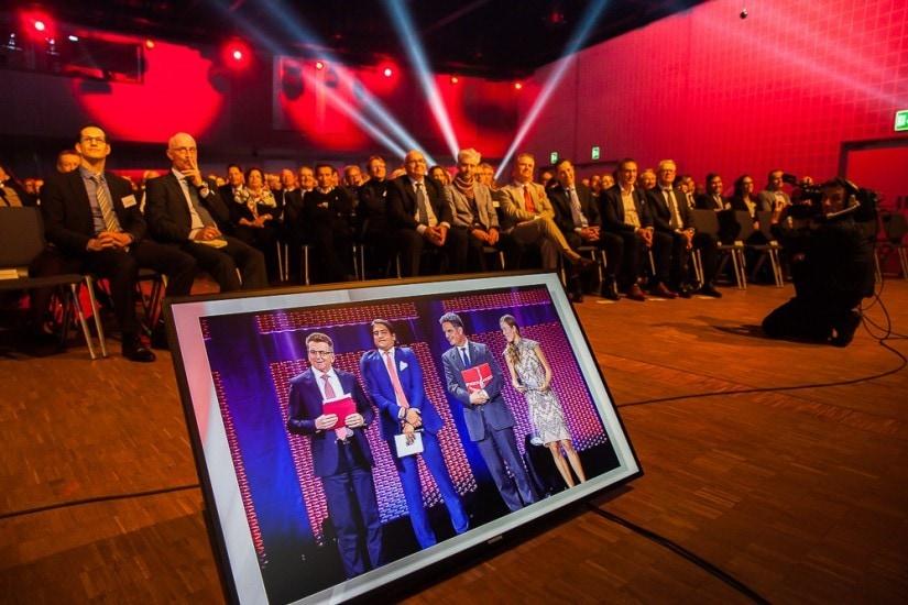 Bildschirm zeigt Personen auf der Bühne, dahinter Publikum im Saal.