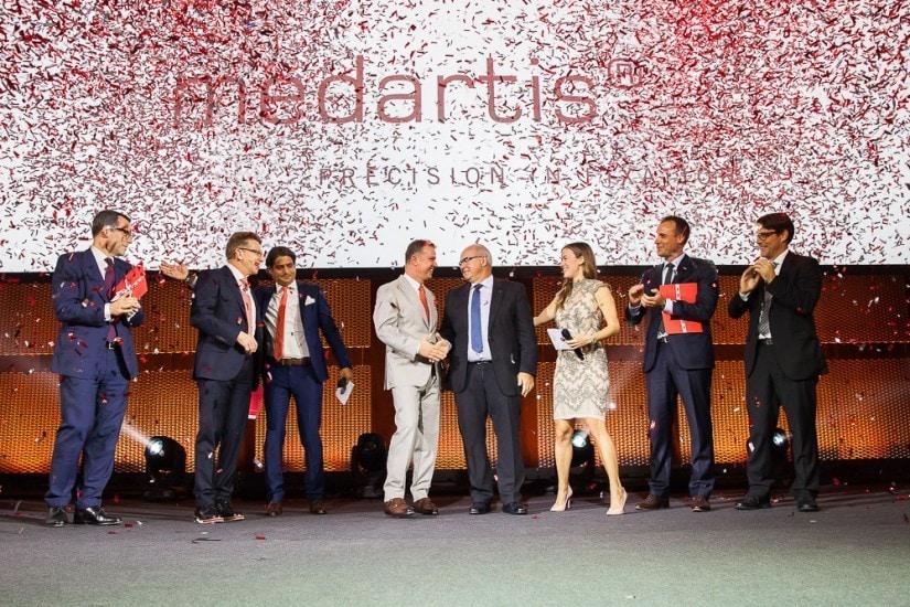 Finalisten stehen auf der Bühne – Konfetti-Regen – Personen applaudieren und gratulieren.