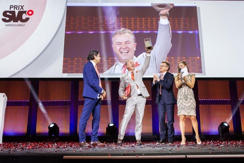 Preisgewinner stemmt freudig seinen Preis in die Höhe. Moderatoren stehen applaudierend daneben.