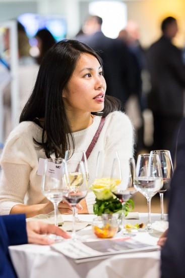 Frau beim Apéro. Viele Weingläser stehen auf einem Bistrotisch.