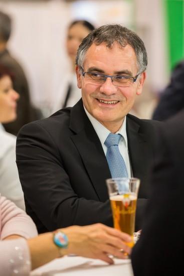 Lachender Mann im Anzug beim Apéro.