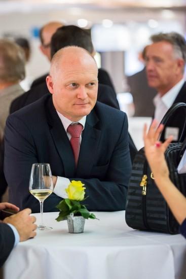 Mann mit blauem Anzug und roter Krawatte steht an einem Bistrotisch.