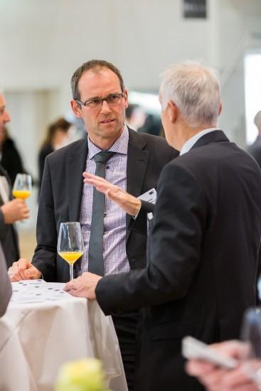 Zwei Männer diskutieren bei einem Glass Orangensaft.