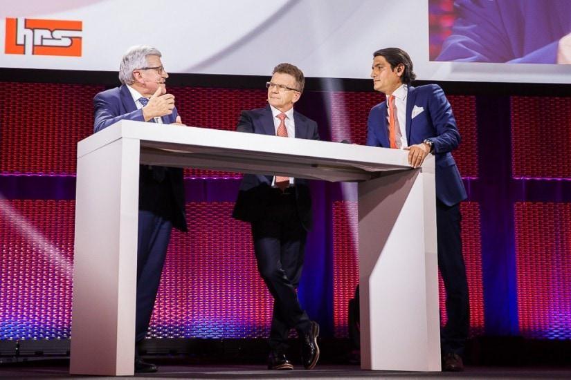 Drei Männer diskutieren an einem Tisch auf der Bühne.