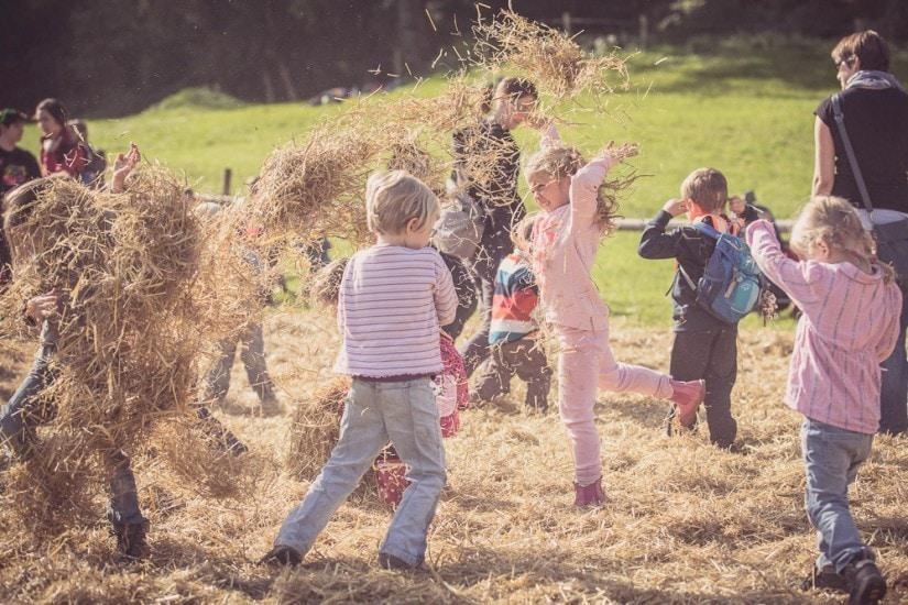 Kinder toben sich in einem Strohhaufen aus.