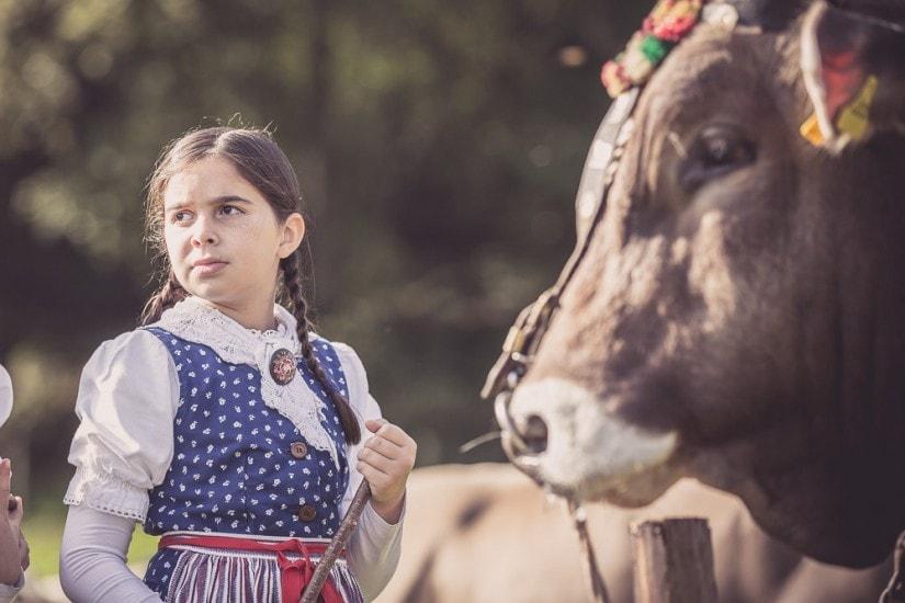 Ein Mädchen steht vor einem Stier.
