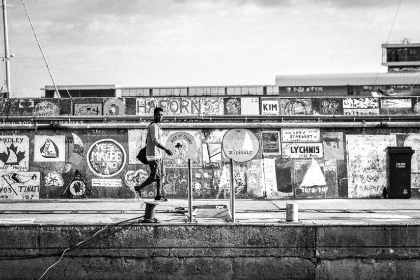 Mann mit Adidasschuhen läuft auf einer Hafenmauer.