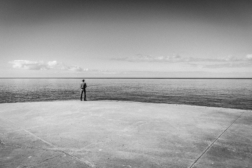 Fischer steht ganz alleine auf einem grossen Platz und fischt im Meer.