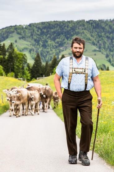 Bauer mit Sennenhemd, im Hintergrund laufen seine Kühe.