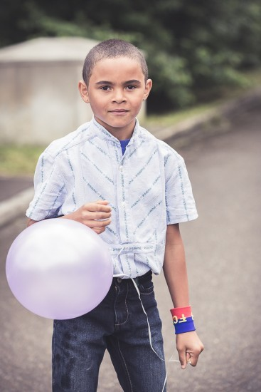 Knabe im Sennenhemd hält einen Ballon in der Hand.