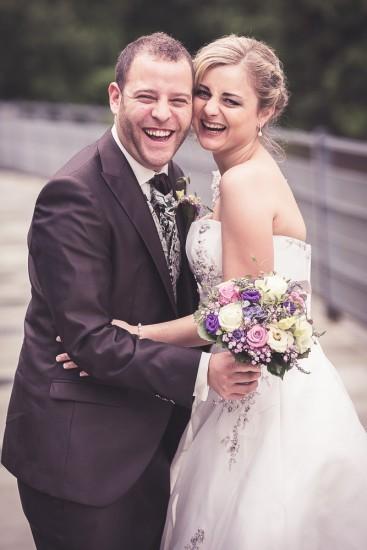 lachendes Brautpaar auf einer Brücke.
