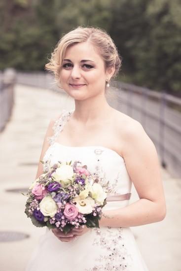 Braut mit schönem Strauss steht auf einer Brücke.