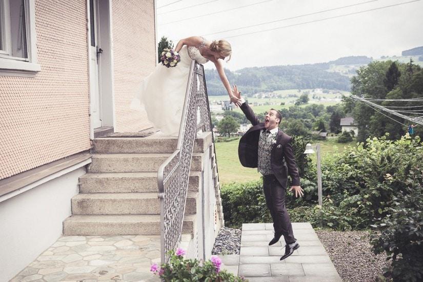 Braut steht oben bei einem Treppenaufgang, Bräutigam versucht hochzuspringen.