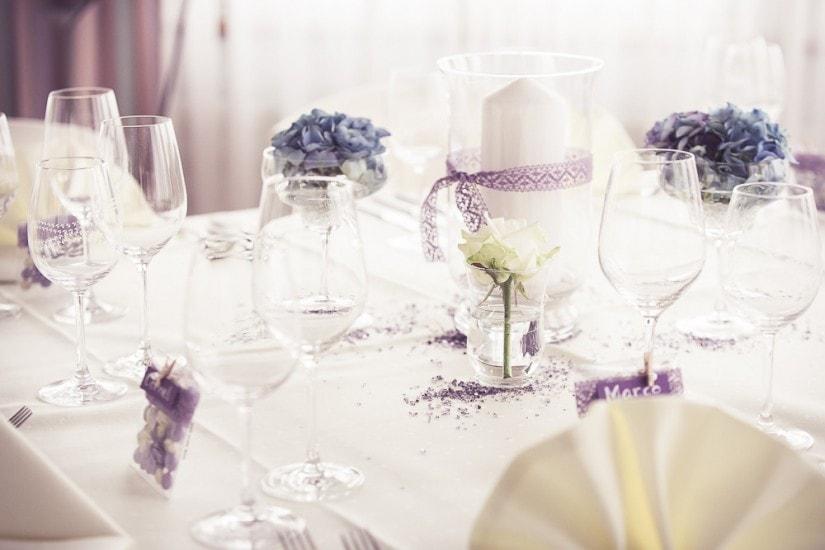 weiss lila Tischdeko, Gläser und Kerzen.