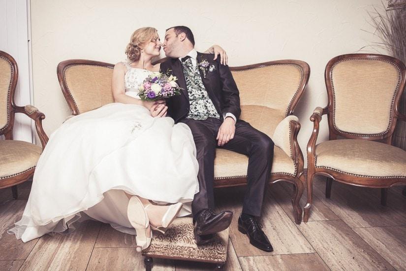 Brautpaar sitzt auf altmödigem Sofa und küsst sich.