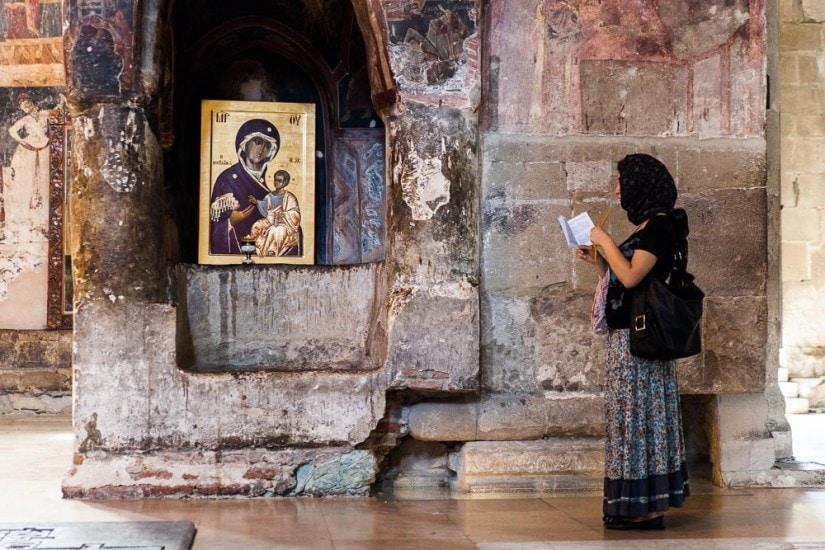 Frau mit Kopftuch steht vor einem goldigen Heiligenbild in einer georgischen Kirche.